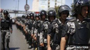 Jordanian riot police walk to maintain order next to protesters holding a demonstration calling for an end to the Israeli offensive in the Gaza Strip, in Amman August 1