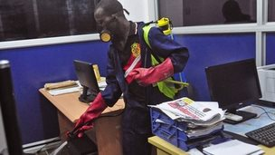 An employee of the Monrovia City Corporation sprays disinfectant inside a government building in a bid to prevent the spread of the deadly Ebola virus (1 August 2014)
