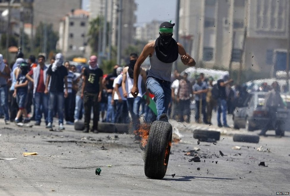 Palestinian protester kicks a burning tyre during clashes with Israeli troops at a protest against the Israeli offensive in Gaza, outside Israel's Ofer military prison near the West Bank city of Ramallah