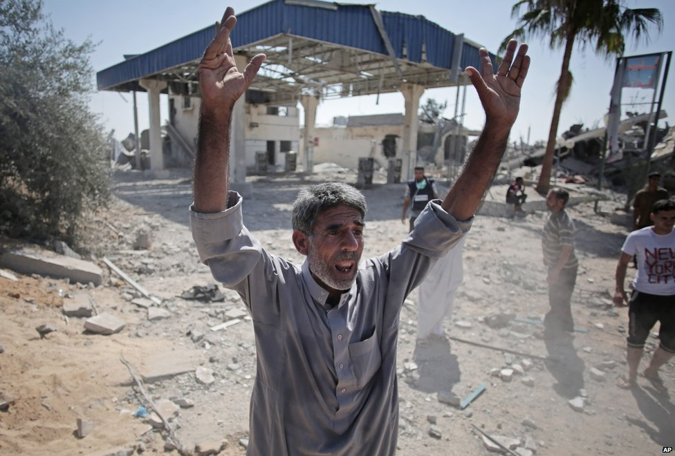 Palestinian man reacts after seeing the ruins of houses caused by Israeli strikes in the village of Khuzaa