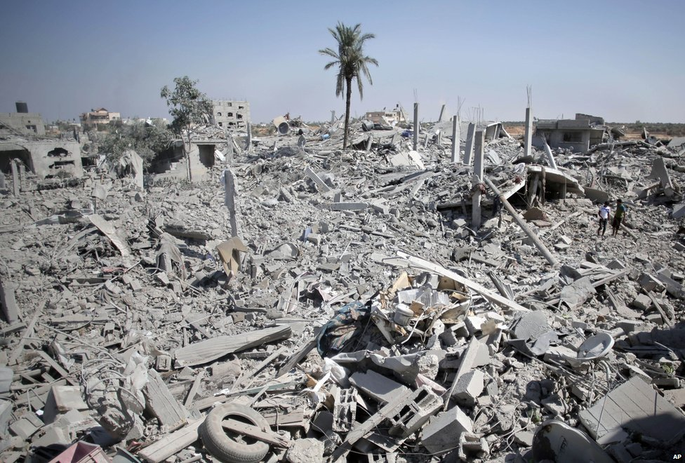 Palestinians inspect the damage of their destroyed houses following Israeli strikes in the village of Khuzaa Gaza