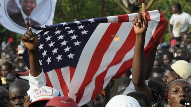 Kenyans holds up the US flag as they celebrate after the inauguration of US president Barack Obama's on 20 January 2009 in Kisumu, Kenya