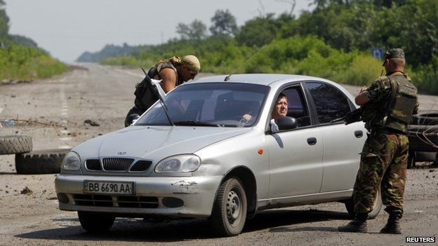 Ukrainian army servicemen check a car at a checkpoint outside the eastern Ukrainian village of Nikishyne (1 August 2014)