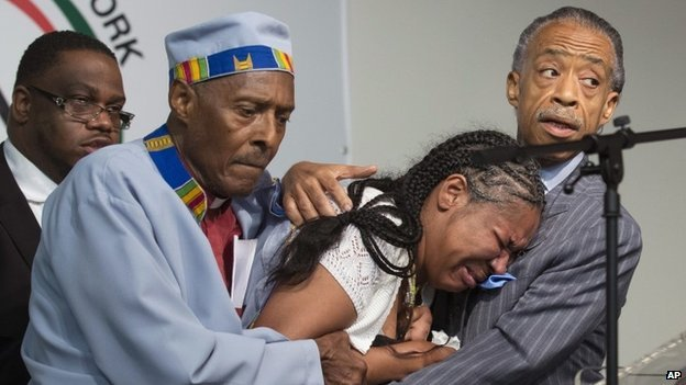 Esaw Garner, center, wife of Eric Garner, breaks down in the arms of Rev Herbert Daughtry and Rev Al Sharpton
