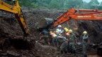 rescue workers dig in the mud