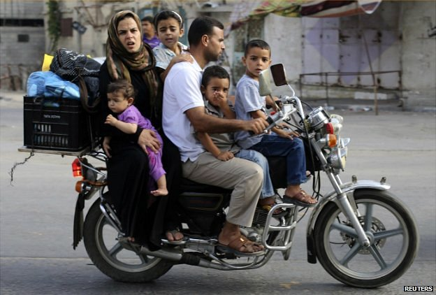 A Palestinian family flee their house in Khan Younis, Gaza, on a motorcycle - 1 August 2014