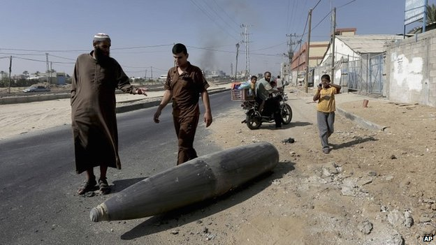 Palestinians look at an unexploded Israeli shell that landed on a road in the Gaza Strip - 1 August 2014