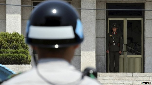 A North Korea soldier looks towards a South Korea soldier at the border - 14 May 2014