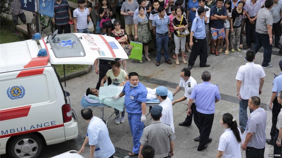 Medical personnel transport a victim (C) at a hospital after an explosion at a factory in Kunshan, 2 Aug