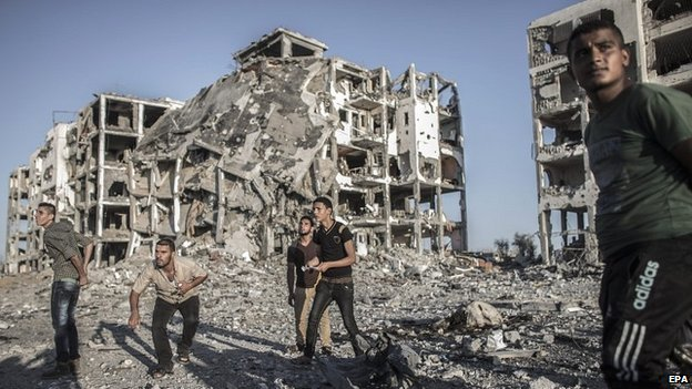 Palestinians try to take cover as they wait for an Israeli airstrike in Beit Lahia, northern Gaza - 2 August 2014