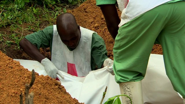 Four-month-old Ebola victim, Fayah, from the affected village of Gueckedou, Guinea, is buried by aid workers