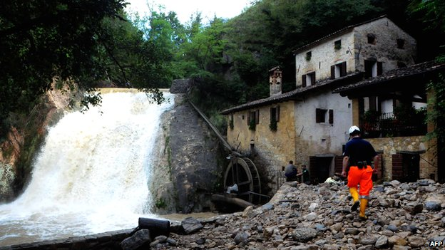 Italian rescue workers try to protect the 17th-Century Molinetto della Croda mill against the overflowing Lierza River following flash floods in Refrontolo, north of Venice
