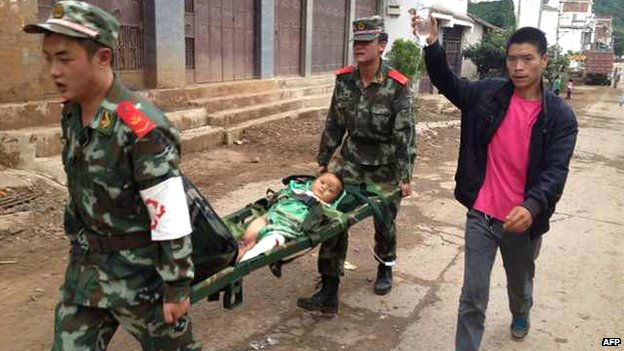 Rescuers carry a child on a stretcher in Ludian county in Zhaotong, in south-west China's Yunnan province