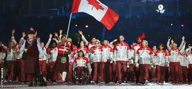Susan Nattras carries the Canadian flag at the opening ceremony