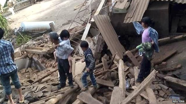 People walk among debris after an earthquake hit Ludian county, Yunnan province