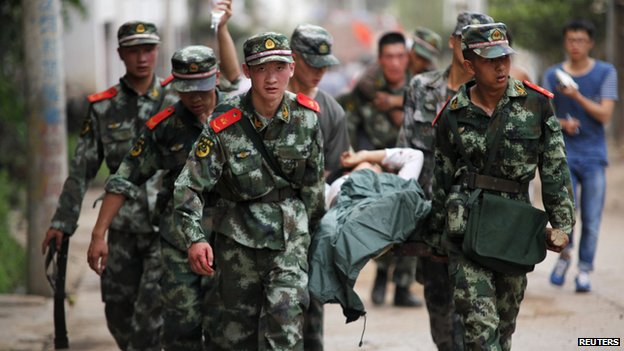 Paramilitary policemen carry an injured resident on a stretcher after an earthquake hit Ludian county of Zhaotong, Yunnan province August 3, 2014