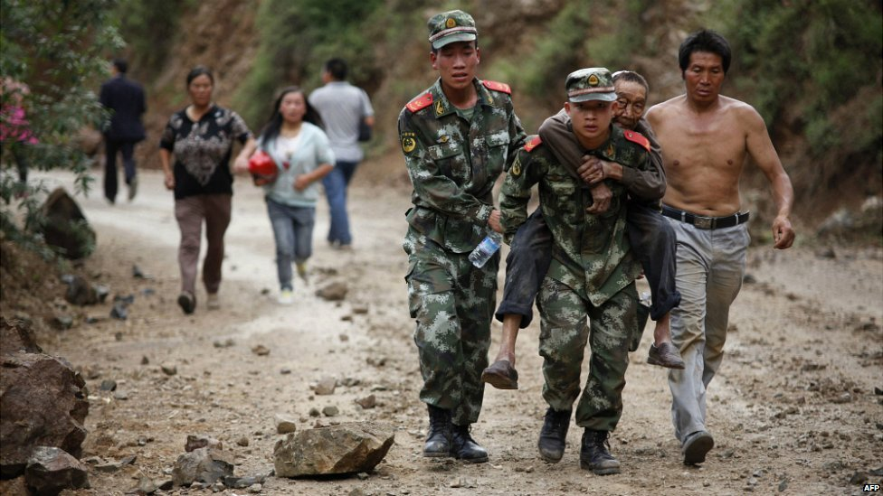 Chinese rescuers carry an injured resident after the earthquake in Yunnan province- 3 August 2014