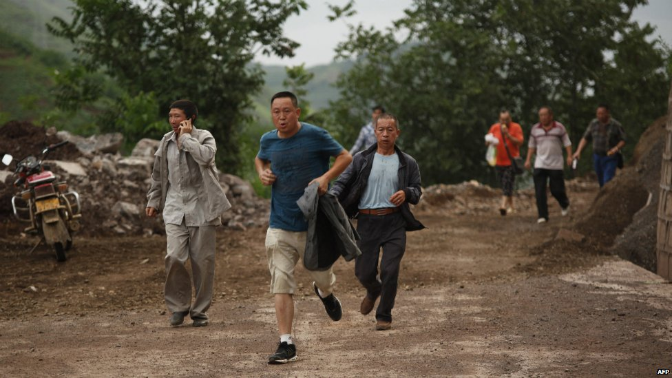 Residents flee a landslide that was caused by the earthquake in Yunnan province - 3 August 2014