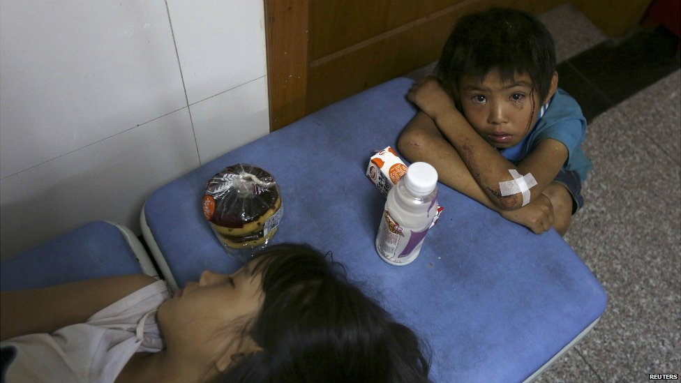 A boy cries next to his sister at a hospital after they were both injured by the earthquake in Yunnan province - 3 August 2014