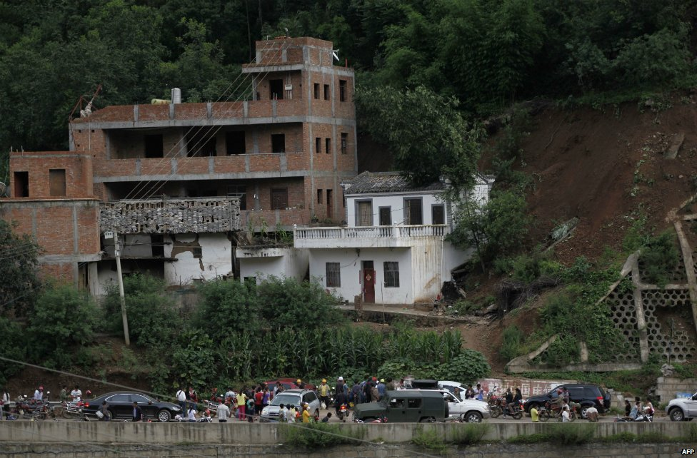 Residents gather near damaged houses following the earthquake in Yunnan province - 3 August 2014