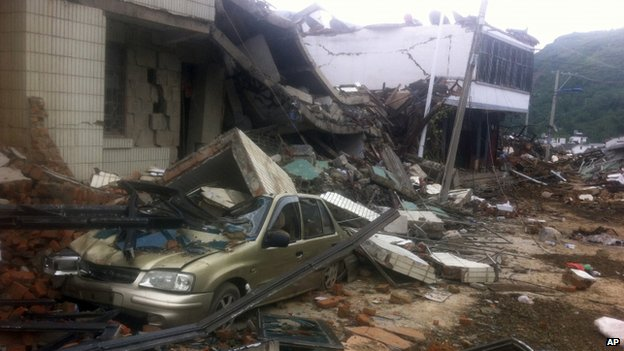 A car covered with rubble in Longtoushan, Yunnan province, on 4 August 2014