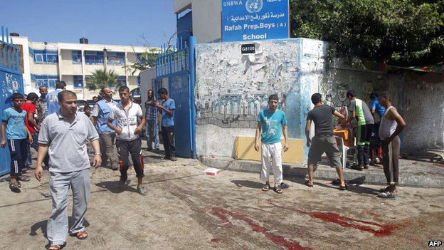 Palestinian walk past trails of blood following an Israeli military strike on the school in Rafah