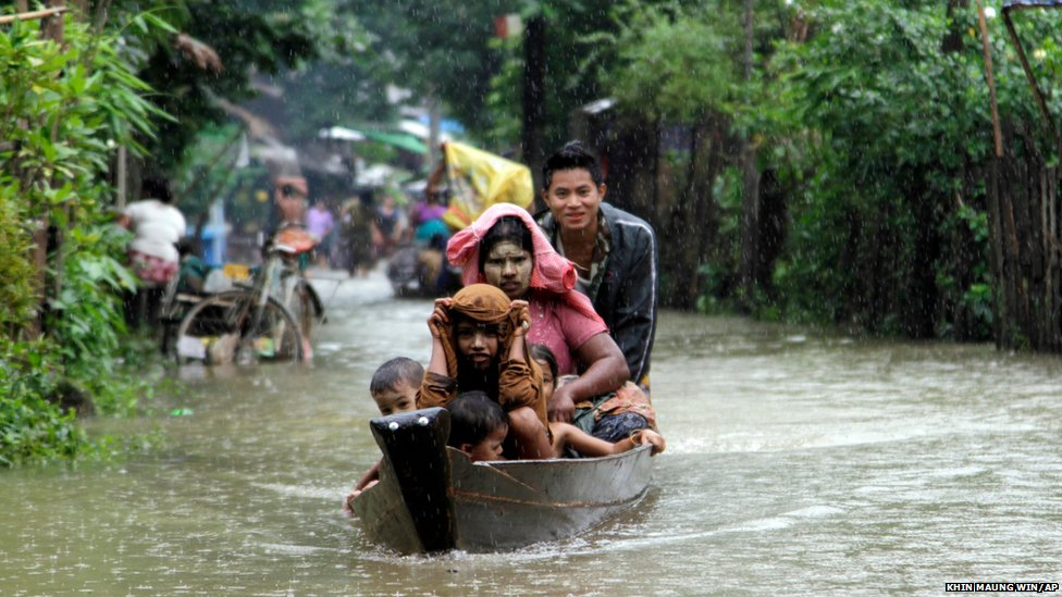 Local residents ride a boat on a flooded road by the Bago river