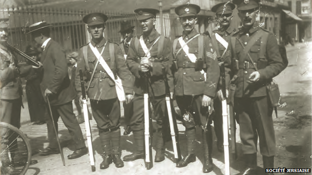 Men holding rifles outside Cattle Market