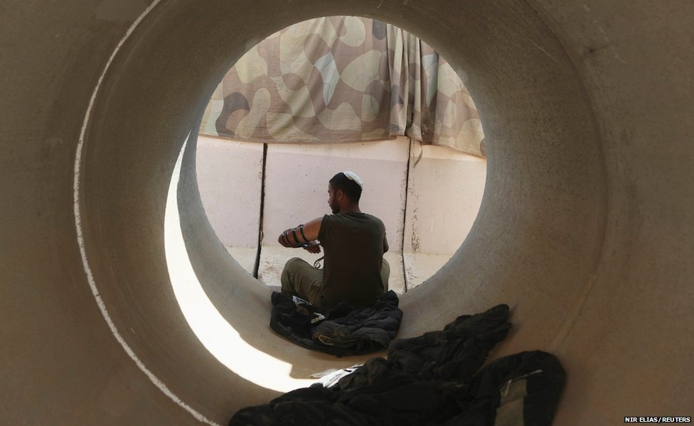An Israeli soldier prepares to pray as he sits in a concrete pipe used as a bomb shelter near the border with the Gaza Strip