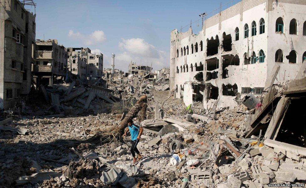A Palestinian man walks amidst the rubble in the Shejaia neighbourhood, Gaza