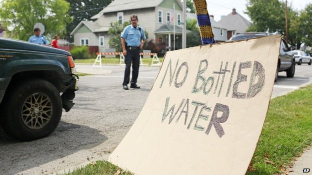 Toledo police officers direct traffic near a water distribution point at Waite High School 3 August 2014