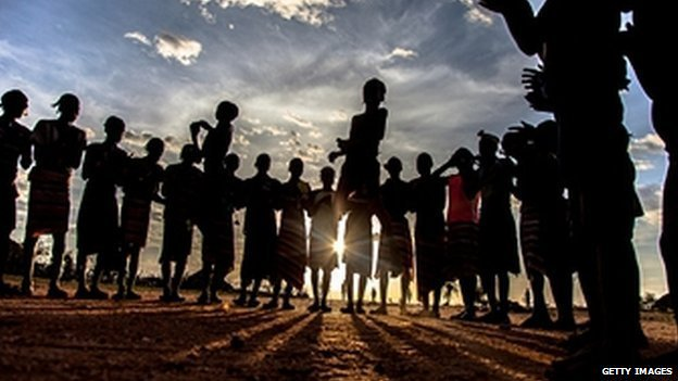Backlit people dance at sunset in Omo valley, south Ethiopia