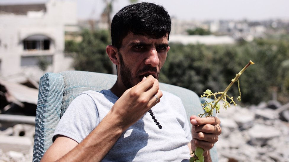 Man in Beit Hanoun eats grapes on the rubble of his home. Aug 2014
