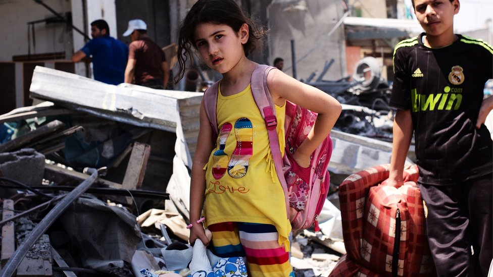 Child gather possessions from ruins of home in Beit Hanoun. Aug 2014