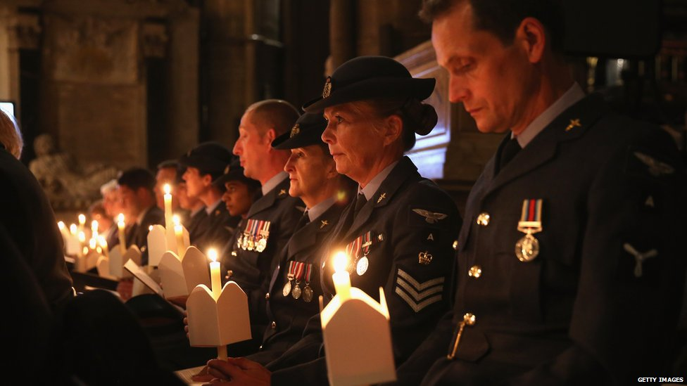 The congregation at a service in Westminster Abbey hold candles