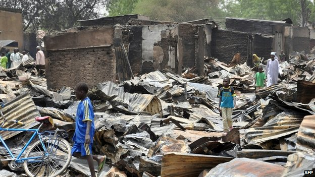 A boy walks past burnt shops at Ngumborum central market on 11 May 2014 at Ngala in Gamboru Ngala district, Borno State