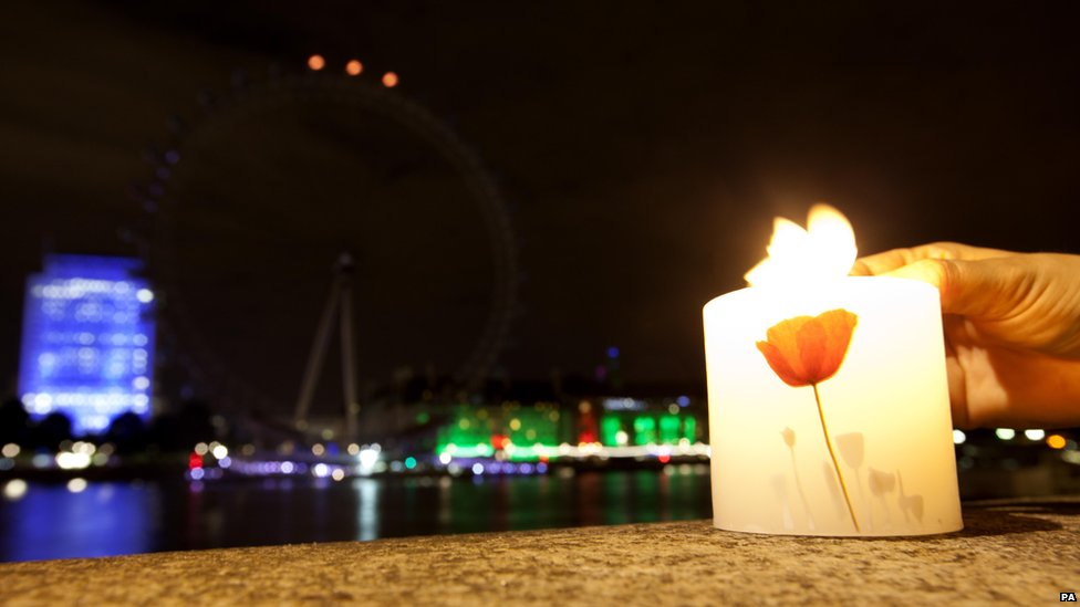 A candle is lit as the London Eye on London's South Bank has its lights switched off