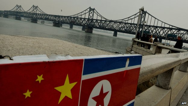 The Chinese and North Korean flags attached to a railing as trucks carrying Chinese-made goods cross into North Korea on the Sino-Korean Friendship Bridge at the Chinese border town of Dandong on 18 December 2013