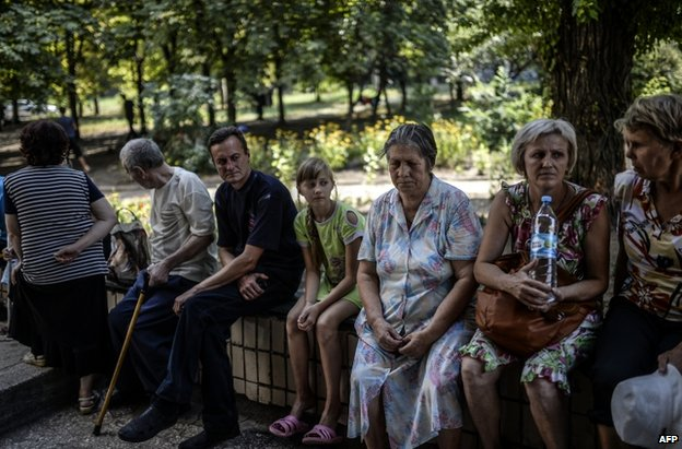 Civilians outside a rebel-run hostel in the city of Donetsk, 4 August