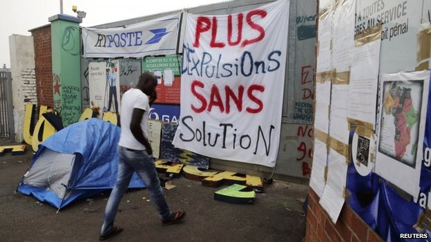 A migrant goes inside in a squat opened by activists from the No Borders UK network in a former recycling factory in Calais August