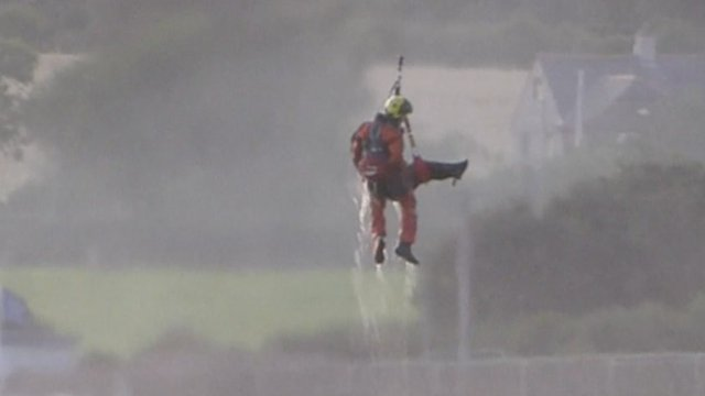 An RAF Valley helicopter crew member rescues one of the men