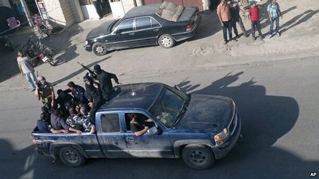 Gunmen driving away in Arsal, a Sunni Muslim town on Lebanon's border with Syria, on 2 August 2014.