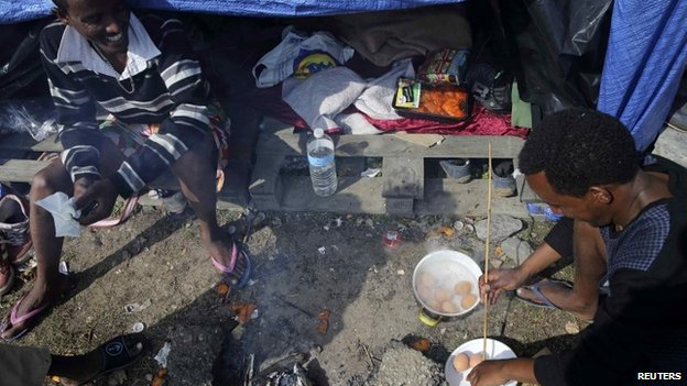 "An Eritrean migrant cooks eggs outside his shelter in the ""jungle"" close to a chemical factory in Calais"