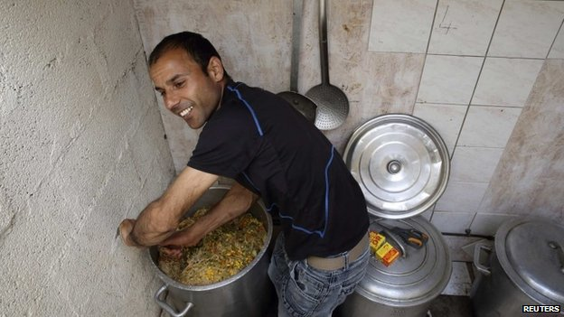 Afghan migrant Rahman Jan Safi prepares a meal for asylum seekers in Calais, northern France