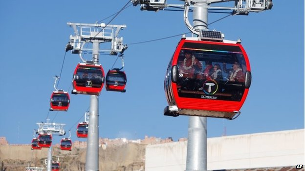 President Evo Morales waves from inside the cable car on the right, during the inauguration ceremony in La Paz