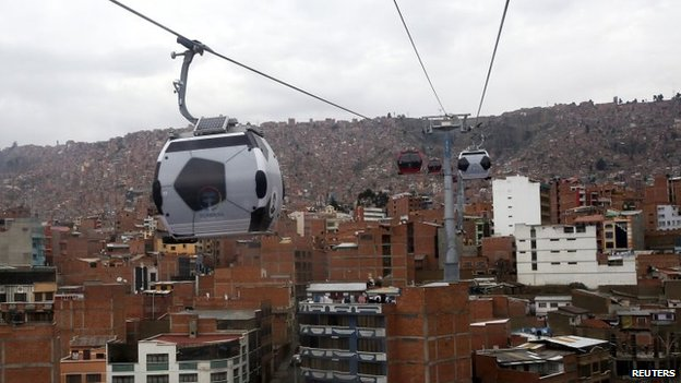 Cable cars decorated to look like soccer balls are pictured over La Paz on 24 June, 2014.