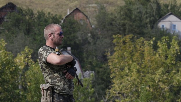 An armed pro-Russian separatist stands guard at a checkpoint in the settlement of Yasynuvata outside Donetsk, 5 August 2014.