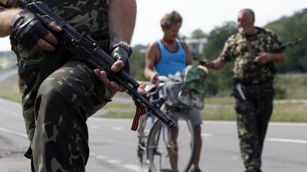 Armed pro-Russian separatists stand guard at a checkpoint in the settlement of Yasynuvata outside Donetsk, on 5 August 2014.