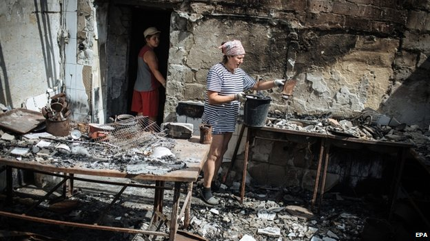 Galina Bogdanova and her son tidy up her destroyed cafe in the eastern Ukrainian city Slaviansk on 5 August 2014.