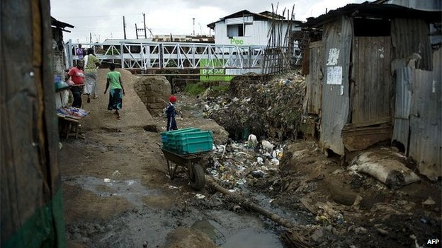 People walk past an open sewer on 8 June 2012 at Kibera slum in Nairobi